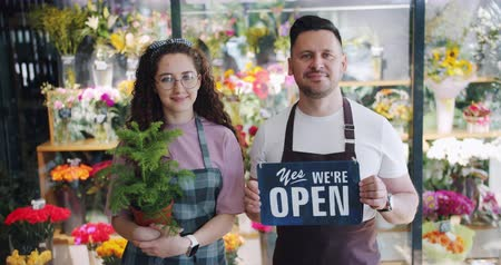 slate : Couple of florists holding open slate and green plant standing together in flower shop smiling looking at camera with colorful beautiful bouquets in background. Stock Footage