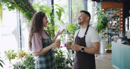 zum mitnehmen : Joyful colleagues florists man and woman are chatting and laughing holding to go coffee at work during lunch break. Happy people and small business concept. Videos