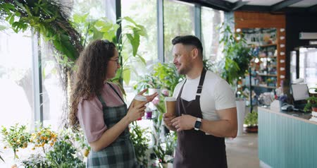 продавщица : Man and woman cheerful florists are talking and smiling holding to go coffee during break in flower shop. Communication, relaxation and youth concept.