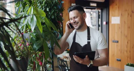 florista : Slow motion of flower shop manager talking on mobile phone and using tablet at work looking at beautiful plants and smiling. People, retailing and communication concept.