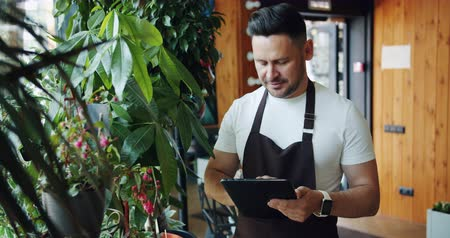 rachunkowość : Flower shop manager touching plants smiling and using tablet in store working alone enjoying blooming greenery in workplace. Modern technology and nature concept. Wideo