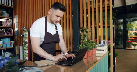 rachunkowość : Entrepreneur working with laptop in flower shop typing and writing in notebook busy with accountancy. Beautiful green plants and bloomings are visible in background. Wideo