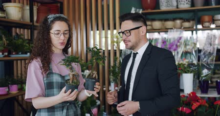 describing : Cute florist friendly cheerful girl is describing beautiful green plants to bearded man in flowers shop standing together holding pots and talking. Business and people concept.