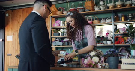 платить : Businessman bearded young man is buying flowers in shop and paying with credit card talking to saleswoman and smiling. Business, people and gifts concept.