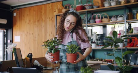 fartuch : Slow motion of young florist attractive woman taking order on mobile phone talking holding plants then writing in notebook. Business and people concept.