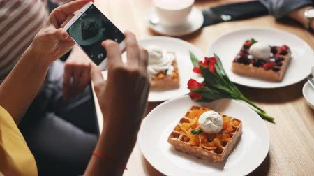 изображение : Cafe customer girl is taking pictures of tasty food using smartphone camera touching screen using modern device. Lifestyle, dining out and youth concept. Стоковые видеозаписи