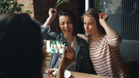 enjoyable : Female friends taking pictures in cafe posing with silly grimaces using smartphone touching screen enjoying leisure time together. Happiness and youth concept.