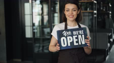 arduvaz : Portrait of happy businesswoman in apron holding open sign standing in new cafe smiling looking at camera welcoming customers. Business and people concept. Stok Video
