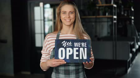 garçonete : Portrait of pretty young girl standing in cafe holding open sign welcoming customers looking at camera and smiling. People, business and start-up concept.
