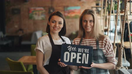 proprietário : Portrait of happy girls waitresses in aprons holding we are open sign standing in cozy cafe smiling looking at camera. Modern business and people concept.