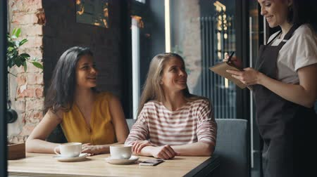 diner : Joyful friends young women are ordering food in cafe talking to friendly female waitress smiling sitting at table together. Modern lifestyle and lunch time concept. Stock Footage