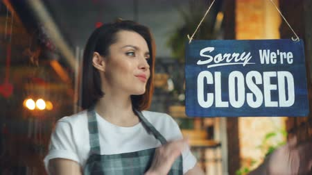 zavřít : Attractive young waitress changing closed to open sign on cafe door smiling looking outside through glass. Happy employees, business and people concept.