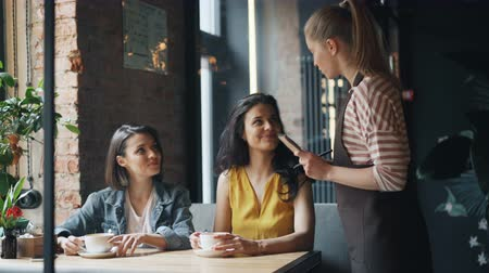 cortes : Cheerful friends attractive young women are chatting in cafe then talking to waitress in apron making order smiling. Happy youth and modern lifestyle concept. Vídeos
