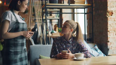 conveniente : Female customer pretty girl is making online payment with smartphone paying for food in cafe smiling talking to friendly waitress. People, technology and finance concept. Stock Footage