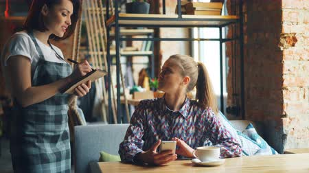 cortes : Pretty girl using smartphone in coffee house then ordering from friendly waitress talking to woman in apron smiling. Modern technology and business concept.