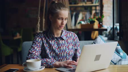 e learning : Attractive female student is studying in cafe using laptop smiling looking at screen typing sitting at table alone. Modern technology and education concept. Stock Footage