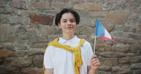 národnost : Portrait of joyful French teenager holding national flag of France smiling outdoors standing in the street alone looking at camera. People and patriotism concept. Dostupné videozáznamy