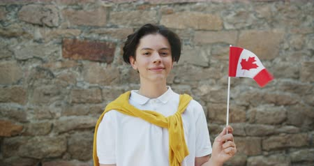 canadian maple leaf : Portrait of cheerful Canadian teenager holding national flag of Canada smiling looking at camera standing outdoors alone with brick wall in background.