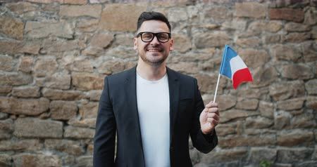 büszke : Happy young man is holding national flag of France standing outdoors smiling looking at camera feeling patriotic and proud. People and nationality concept.