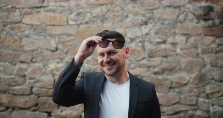 charisma : Slow motion portrait of stylish bearded guy taking off sunglasses smiling outdoors standing alone with brick wall in background. People and identity concept.