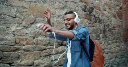 rapper : Slow motion of joyful African American guy listening to music in headphones outdoors holding smartphone walking and dancing in the street. People and happiness concept.