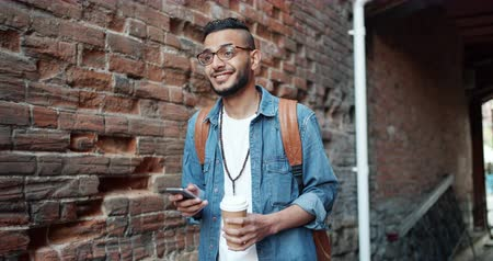 feliz : Slow motion of Arabian guy using gadget smartphone holding coffee walking outdoors in the street near brick wall smiling touching screen. Millennials and devices concept.