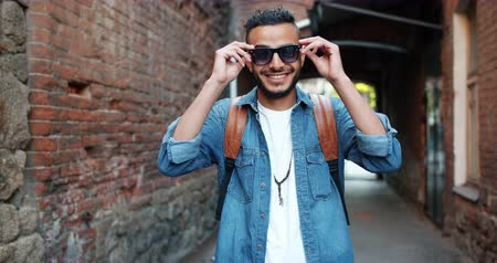 харизматический : Portrait of good-looking middle Eastern man taking off sunglasses smiling standing outdoors in the street in city with hapy face. Youth and style concept.