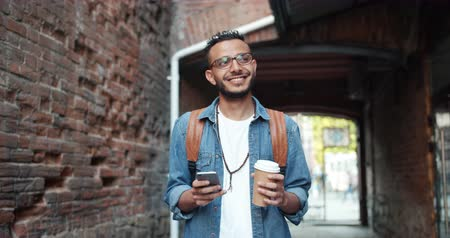 miçanga : Smiling Middle Eastern guy using smartphone outdoors and holding to go coffee standing alone in the street enjoying communication and contemporary device.