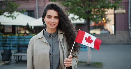 гражданство : Portrait of pretty young lady patriot holding Canadian flag in the street smiling looking at camera on windy day. Beautiful people and nationality concept.