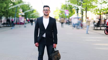 стоять : Zoom-out time lapse of handsome guy with bag standing outdoors in the street wearing trendy clothing and glasses looking at camera while people walking by.