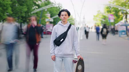 outsider : Time lapse of handsome teen standing alone outside in the street with skateboard looking at camera on summer day. Youth culture, hobby and people concept. Stock Footage