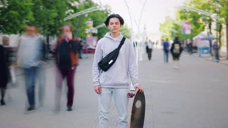 outsider : Zoom-out time lapse of young skateboarder handsome boy standing outdoors in street with board looking at camera. People, active lifestyle and city concept.