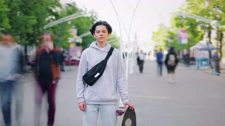 camera move : Time lapse portrait of stylish teenage skateboarder standing in the street alone holding skateboard and looking at camera while crowd is rushing around.