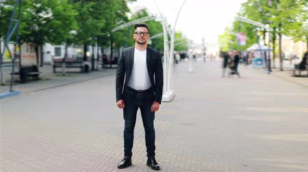 személyiség : Time lapse of handsome young businessman standing outdoors in pedestrian street wearing stylish clothing looking at camera. People and modern city concept.