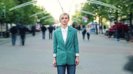 daily life : Time lapse of cute blond lady standing in the street alone among crowd of people looking at camera with serious face. Loneliness, urban life and youth concept. Stock Footage