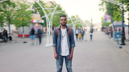 outsider : Zoom-out time lapse of attractive young man Arab standing in busy street with backpack looking at camera with serious face. Life, people and society concept.