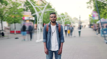 személyiség : Time lapse portrait of Middle Eastern man with backpack standing in the street alone looking at camera when people are passing by. Youth and travelling concept.