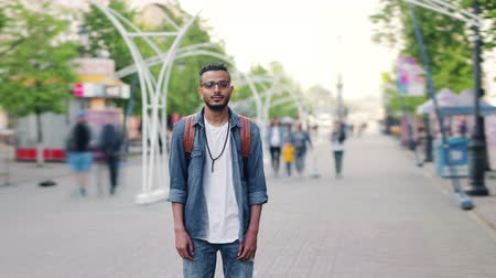 yaya : Time lapse of bearded Arab standing in the city street alone with backpack looking at camera with serious face. Modern lifestyle, people and urban life concept. Stok Video