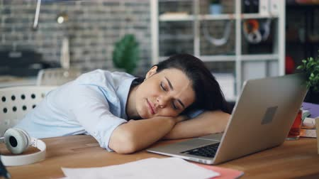 tezgâhtar : Portrait of attractive young lady office worker sleeping at work on desk relaxing during workday. Modern lifestyle, tired people and business concept.