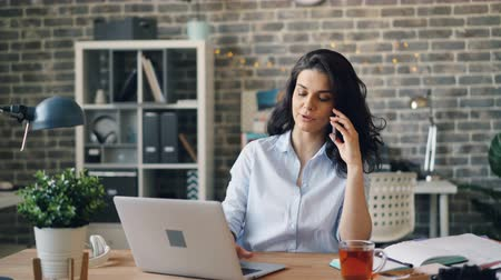 jovem : Beautiful businesswoman is talking on mobile phone and typing on laptop in modern office communicating with business partners. People and work concept. Stock Footage