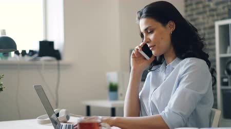 enjoyable : Happy office worker pretty girl is laughing talking on mobile phone and working with laptop communicating with business partners. Youth and work concept. Stock Footage