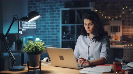 turning off : Young woman is turning off laptop and light in office at night and leaving work after long workday. Hard-working people, overtime job and millennials concept. Stock Footage