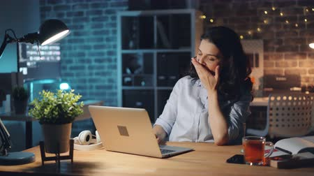 workload : Tired office worker pretty girl is using computer and yawning working late at night alone sitting at desk touching face feeling exhausted. Overwork and youth concept. Stock Footage
