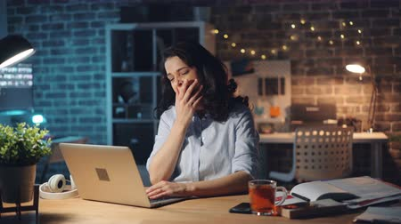 workload : Exhausted young lady is typing with laptop then yawning working in office at night being exhausted at work. Business, hard-working people and millennials concept. Stock Footage