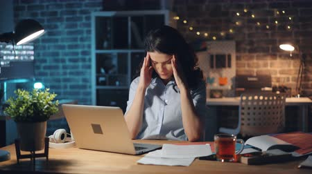 workload : Exhausted office worker pretty girl is typing on laptop then reading document feeling headache working at night in dark workplace. People and workaholism concept.