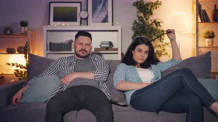 watch tv : Young family man and woman watching boring movie on TV at home sitting on couch together with unhappy bored faces. People, house and television concept. Stock Footage