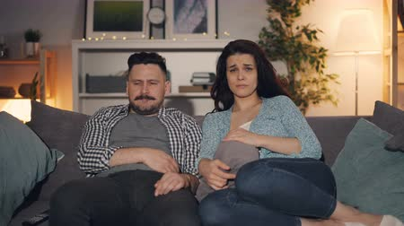 késő : Husband and wife beautiful young people are watching drama on TV with sad faces sitting on couch in house at night focused on movie. Youth and mass media concept.