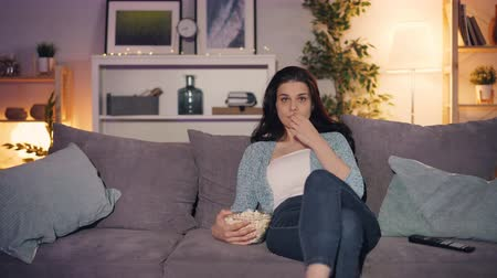 pipoca : Girl is watching TV and eating popcorn at home at night when man is jumping from behind sofa laughing making surprise. People, fun and relationship concept. Stock Footage