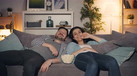 コミカル : Happy young couple watching funny show on TV laughing eating popcorn at home lying on sofa together late at night. People, fun and mass media concept. 動画素材