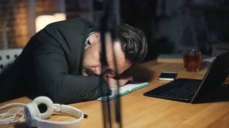 workload : Portrait of tired handsome man sleeping on desk in dark office late at night lying on desktop with closed eyes. People, modern lifestyle and business concept.